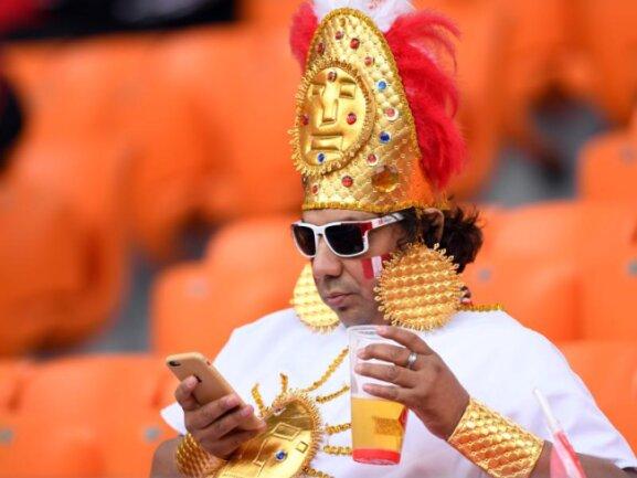 <b>Inka</b><br/>Ein kostümierter Fan des peruanischen Teams hat es sich vor dem Anpfiff des Spiels gegen Frankreich im Jekaterinburg-Stadion mit Getränk und Smartphone bequem gemacht. Foto:Marius Becker<br/>21.06.2018 (dpa)