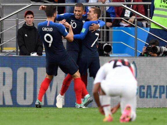 <b>Torjubel</b><br/>Während die Franzosen ihren Sieg-Torschützen Kylian Mbappe feiern, schnürt sich einer Peruaner nach dem entscheidenden Treffer seine Schuhe. Foto:Marius Becker<br/>21.06.2018 (dpa)