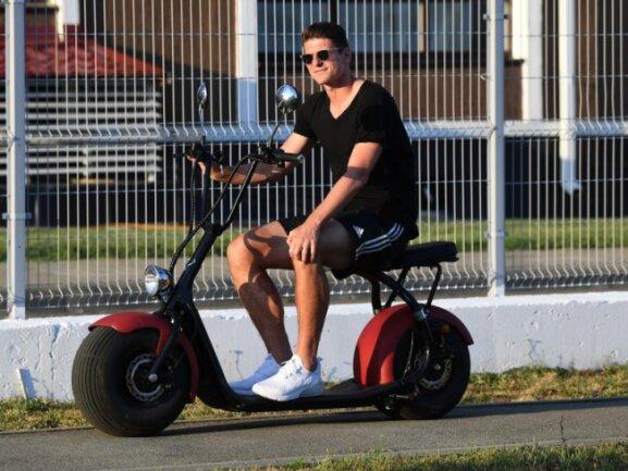 <b>Altersgerecht</b><br/>In Sotschi fährt Mario Gomez, im Gegensatz zu seinen Teamkollegen die einen Segway bevorzugen, auf einem Sitz-Roller vom Trainingsgelände zum Mannschaftshotel. Foto:Ina Fassbender<br/>21.06.2018 (dpa)