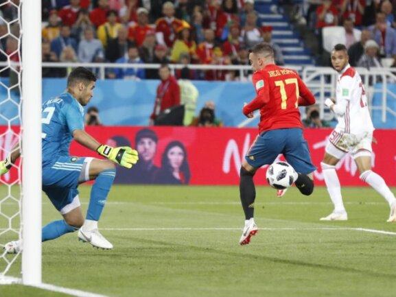 <b>Ausgleich in letzter Minute</b><br/>Spaniens Iago Aspas (M) trifft sehenswert in der letzten Minute gegen Marokkos Torhüter Monir zum im Vorfeld nicht zu erwarteten 2:2. Foto: Petr David Josek/AP<br/>25.06.2018 (dpa)
