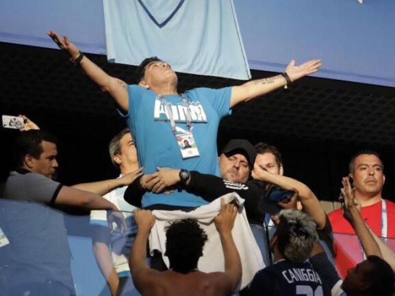 <b>Selbstinszenierung</b><br/>Diego Maradona lässt sich von den argentinischen Fans im Stadion feiern, während ein Bodyguard darum bemüht ist zu verhindern, dass die Fußball-Legende über die Brüstung fällt. Hoffentlich ist der Job gut bezahlt. Foto: Petr David Josek/AP<br/>26.06.2018 (dpa)