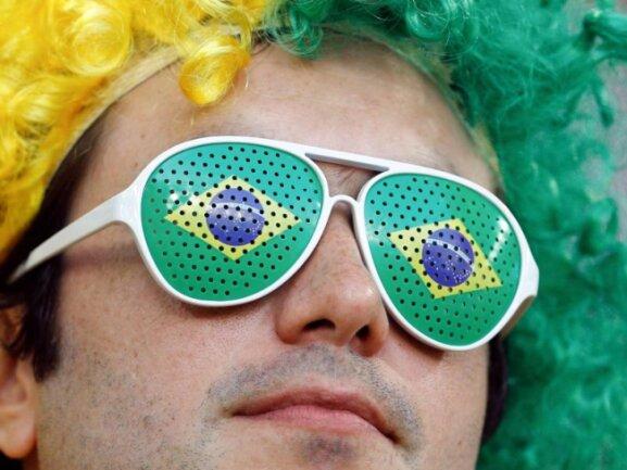 <b>Grüne Brille</b><br/>Ein Brasilien-Fan guckt durch seine grün-gelbe Brasilien-Brille Richtung Spielfeld. Foto: Victor R. Caivano/AP<br/>27.06.2018 (dpa)