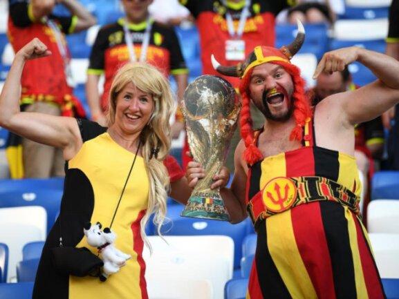 <b>Stark, stärker, Belgien</b><br/>Ein belgisches Paar lässt seine Muskeln spielen und posiert vor dem Spiel gegen England mit einer Nachbildung des WM-Pokals. Foto: Marius Becker<br/>28.06.2018 (dpa)
