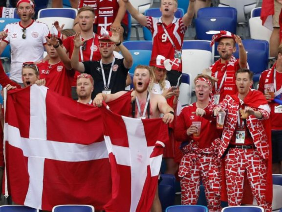 <b>Rot-weiß</b><br/>Fast 3000 Kilometer fern der dänischen Heimat feuern die rot-weiß auftretenden Fans ihre Mannschaft in Nischni Nowgorod gegen Kroatien an. Foto: Darko Bandic/AP<br/>01.07.2018 (dpa)