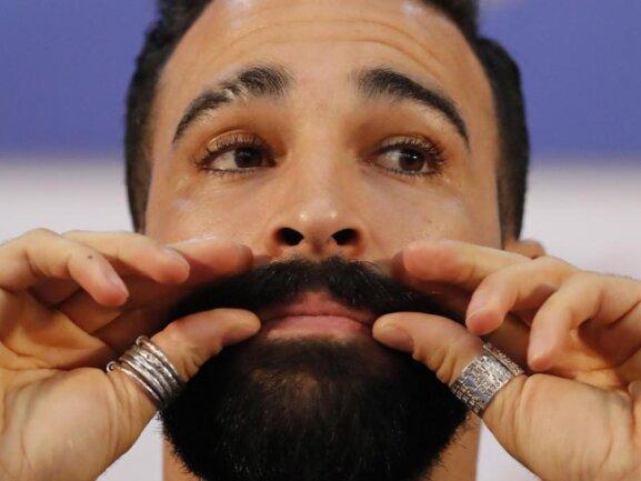 <b>Pogonophil</b><br/>Kein Spitzname, die Bezeichnung für einen Bartliebhaber: Bei der Pressekonferenz Frankreichs vor dem WM-Viertelfinale gegen Uruguay zwirbelt Adil Rami seinen Bart. Foto: David Vincent/AP<br/>04.07.2018 (dpa)