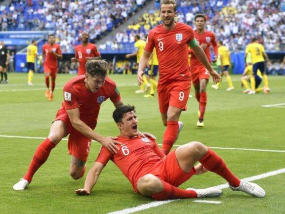 <b>Umwerfend</b><br/>Harry Maguire (M) jubelt am Boden liegend mit John Stones (l) und Harry Kane über sein Tor zur 1:0-Führung für England. Nach dem 2:0-Sieg gegen Schweden stehen die Three Lions im WM-Halbfinale. Foto: Chen Yichen/xinhua<br/>07.07.2018 (dpa)