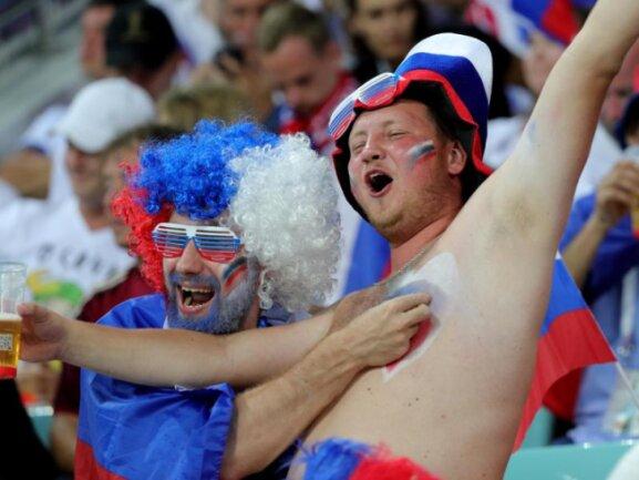 <b>Fan-Vergnügen</b><br/>Zwei vermutlich russische Fußballfans zeigen sich beim Viertelfinale Russlands gege Kroatien in bester Laune. Foto:Christian Charisius<br/>07.07.2018 (dpa)
