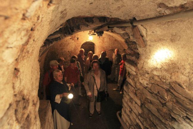 <p>Im düsteren Keller des Gutshauses zeugen dicke Mauern von den mittelalterlichen Ursprüngen der Anlage. Ursula Keller (links) dührte die Besucher am Samstag durch die Kellergewölbe. Sie wohnte bis 1972 im Rittergut.</p>