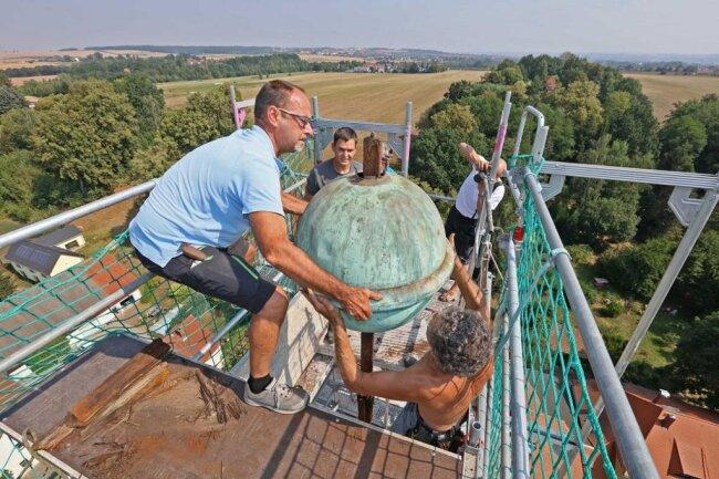 <p>Dachdeckermeister Heiko Winter und Spengler Ezard Schwalbe hievten die Kugel nach unten.</p>