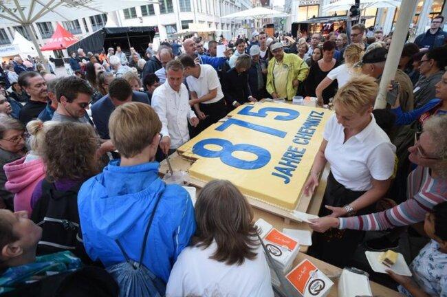 <p>Mit Blick auf das Stadtjubiläum sind aus dem Backwerk 875 Stücke geschnitten und an die Chemnitzer vor der Bühne auf dem Marktplatz verteilt worden.</p>