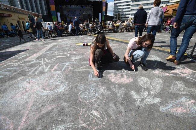 <p>Auf der Brückenstraße malten Kinder mit Kreide einen riesigen Blumenstrauß.</p>