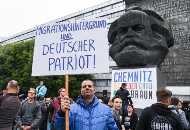 """<p>Ein Teilnehmer der Kundgebung der rechtspopulistischen Bürgerbewegung Pro Chemnitz hält vor dem Karl-Marx-Denkmal ein Schild mit der Aufschrift """"MIGRATIONSHINTERGRUND UND DEUTSCHER PATRIOT!"""" in der Hand.</p>"""