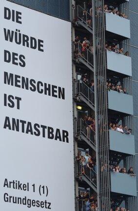 """<p>Im Hochhaus an der Kreuzung zur Augustusburger Straße drängelten sich auf jedem der 14 Balkons übereinander die Zuschauer. Daneben das riesige Transparent """"Die Würde des Menschen ist antastbar. - Artikel 1 Grundgesetz, Stand 27.08.2018""""</p>"""