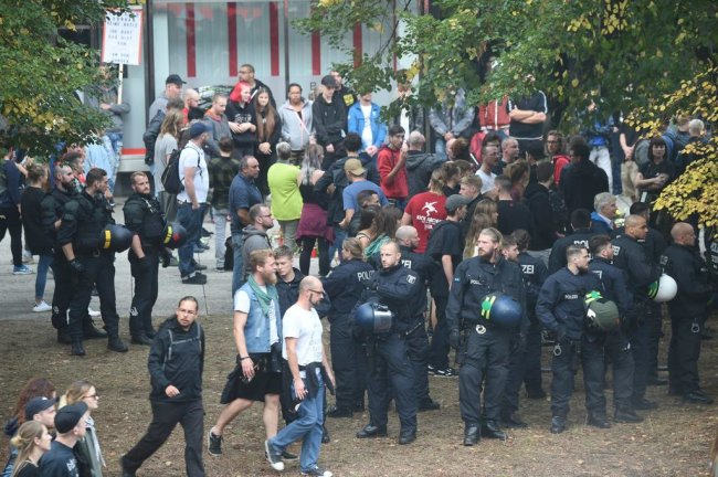 """<p>Rund 100 Personen hatten sich am Tatort versammelt, ein Teil gehörte augenscheinlich dem linken, ein Teil dem rechten Lager an. Es wurde heftig diskutiert. Ein Mann störte sich an einem Plakat der Linken mit der Aufschrift """"Nazis nerven mehr als Wespen"""". Er sei kein Nazi und die, die mit ihm trauern, auch nicht, schrie der Mann. Die Polizei zog zusätzliche Kräfte vor Ort zusammen, die sich zwischen die beiden Lager stellten, aber nicht eingreifen mussten.</p>"""
