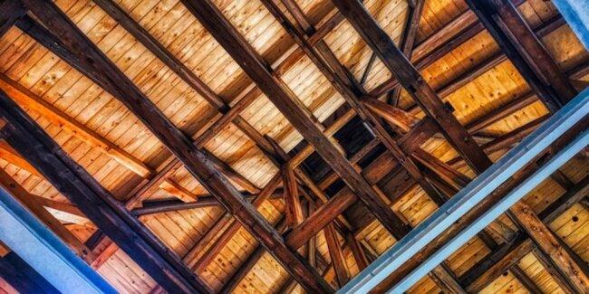 <p>Wellner, Gebäude 1, Dachstuhl. Ein Stück des alten Dachstuhls wurde erhalten. Es handelt sich um die dunklen Balken. Das Foto vereinigt Alt und Neu: Neues Holz, altes Holz und Stahlträger.</p>