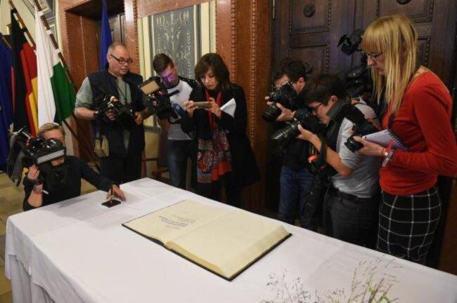 """<p><span class=""""img-info"""">Journalisten fotografieren den Eintrag Steinmeiers ins Goldene Buch der Stadt.</span></p>"""