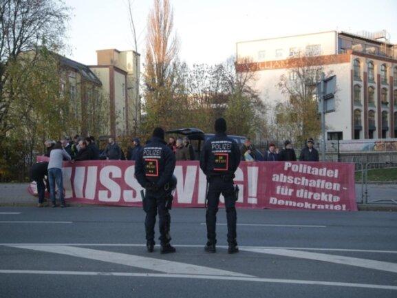 """<p>Erste Demonstranten entrollten """"Merkel muss weg""""-Plakate gegen 16 Uhr.</p>"""