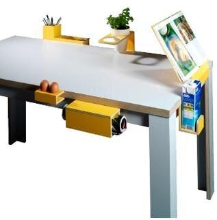 <b>Tisch der vielen Möglichkeiten von Felix Wissing:</b> Er ist so modifiziert, dass man verschiedene Module an der Tischplatte befestigen kann. Es gibt Handtuch- und Kochbuchhalter, Flaschen- und Besteckhalter, sowie tragbare Tabletts und Ein- kaufs- oder Abfalltüten. Die eigentliche Tischoberfiäche befreit sich vom Gedeck.