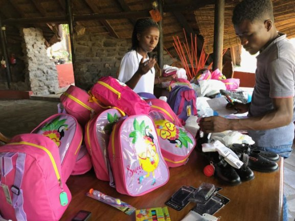 <p>Eric, Pädagogikstudent 1. Studienjahr und Ritha Absolventin 12. Klasse helfen beim Packen der kleinen Rucksäcke für unsere 22 erfolgreichen Schulanfänger</p>
