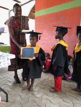 <p>Bertha Kwandu, Vizepräsidentin der Shambyus, überreicht den Kindern die Urkunden für den erfolgreichen Vorschulabschluss</p>