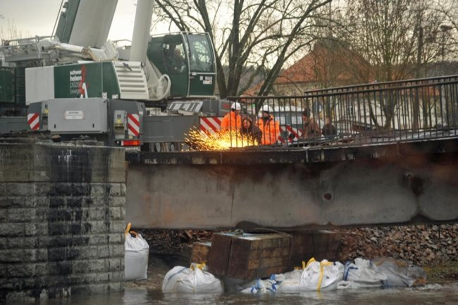 <p>Kurz nach 8 Uhr gab es den entscheidenden Ruck. Mit einem dumpfen Krachen hob sich der Brückenkörper von den Pfeilern, wurde von den beiden Kranen ein Stück stromaufwärts geschwenkt und vor den Pfeilern abgesetzt.</p>