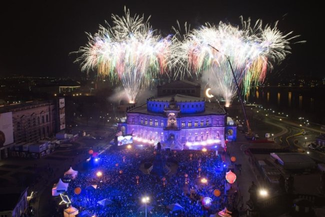 <p>Besucher des Semperopernballs verfolgen auf dem Theaterplatz das Feuerwerk zur Eröffnung vor dem farbig angestrahlten Opernhaus.</p>