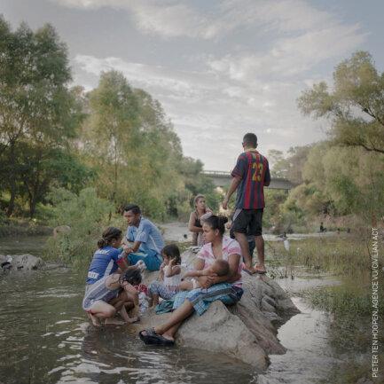 """<p>In einer Fotoserie dokumentierte Fotograf Hoopen die Flucht einer """"Karawane"""" von Menschen in Zentralamerika vor politischer Repression und Gewalt und vor schlechten wirtschaftlichen Bedingungen. Das Foto zeigt Teile einer Gruppe von Geflüchteten, die im Rio Novillero baden, ihre Wäsche waschen und ausruhen. Die Serie bekam den ersten Platzin der Kategorie Weltpresse-Fotoserie des Jahres 2018.</p>"""