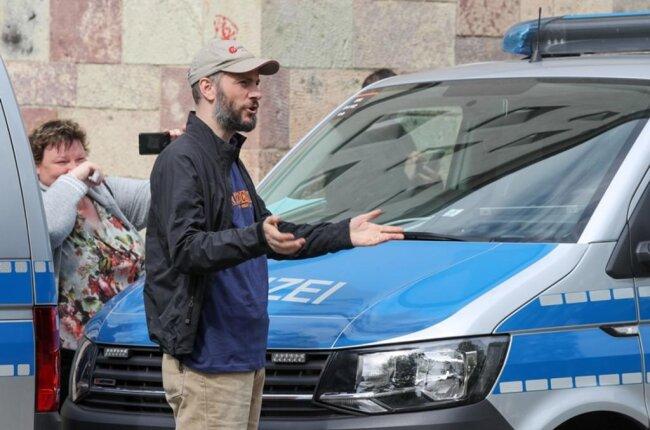 <p>Pro-Chemnitz-Chef Martin Kohlmann steht vor einer Kette aus Polizeifahrzeugen und gestikuliert in Richtung der Gegendemonstranten.</p>