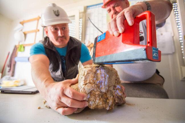 <p>Zwei Mitarbeiter in Pöhla schauen mit einer UV-Lampe, wo sich im Gestein das Mineral befindet.</p>