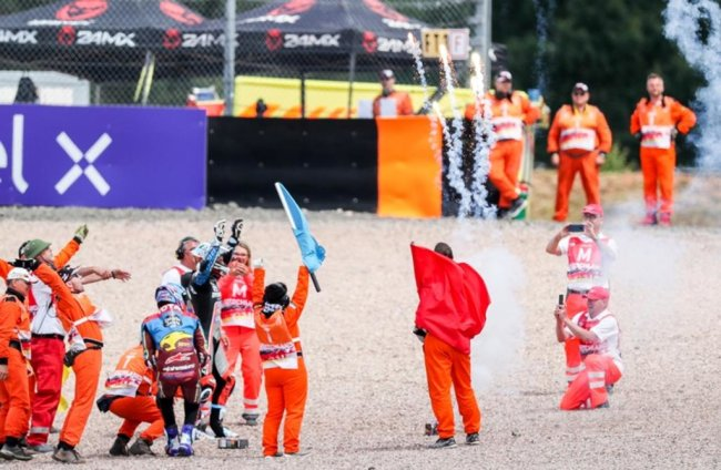 <p>Marcel Schrötter (Deutschland, Dynavolt Intact GP Team, hinten) und Alex Marquez (Spanien, EG 0,0 Marc VDS Team) feiern ihre Platzierungen mit den Streckenposten.</p>
