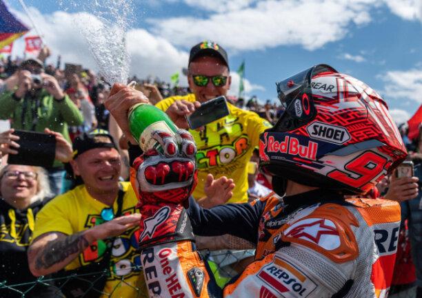 <p>Marquez spritzt nach seinem Sieg mit Sekt auf seine Fans.</p>
