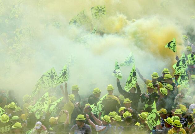 <p>Fans von Valentino Rossi schwenken Fahnen und zünden Nebeltöpfe auf einer Tribüne.</p>