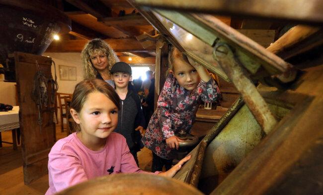 <p>Der originale, über 1 Tonne schwere Walzenstuhl steht nach der Sanierung wieder an seinem Platz. Ema (6), Laura (4) und Oliver (9) durften einen Blick in das Innere werfen.</p>