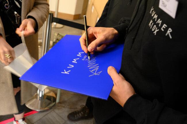 <p>Felix Kummer signiert unermüdlich Platte um Platte.</p>