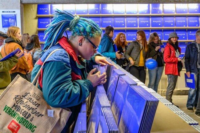 <p>Etliche kennt er persönlich, schüttelt Hände, signiert die knallblauen Vinylplatten, CDs und Kassetten und sogar einen hingehaltenen Turnschuh.</p>