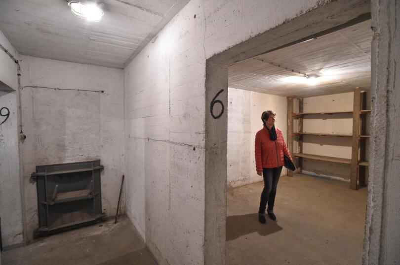 """<p><span style=""""color:#1f497d"""">Objektbetreuerin Anke Förster von der GGG in einem der Räume, in dem ein Holzregal steht. Links ist eine Verbindungsluke zu sehen.</span></p>"""