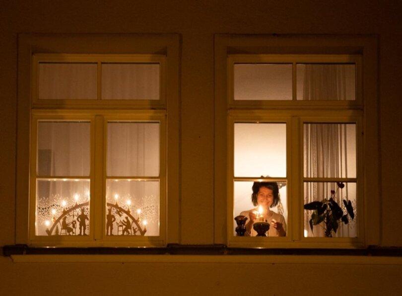 <p>Carmen Hickmann beim Entzünden einer Kerze. Punkt 21 Uhr am Samstagabend schaltete die Annaberger Familie zudem ihren Schwibbogen an.</p>