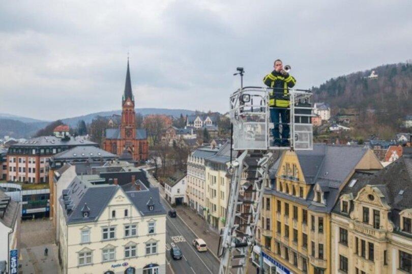 <p>Auf der Drehleiter der Feuerwehr der Stadt Aue-Bad Schlema stehend, hat Sebastian Schlesinger vom Posaunenchor der St.-Nikolai-Kirchgemeinde am 3. April in 30 Metern Höhe über dem Altmarkt das Steigerlied gespielt.</p>