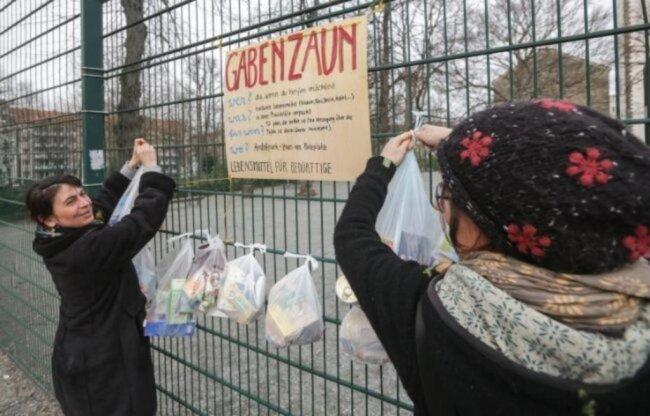 <p>Constanze Gröer und Mandy Arnold (von links) bestücken in Chemnitz den Gabenzaun regelmäßig mit Tüten voller Lebensmittel.</p>