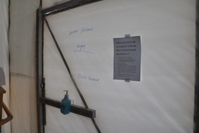 <p>Kunststoffplanen, Klebeband, Holzleisten und Stop-Schilder trennen die Corona-Isolierstation vom Rest des Krankenhauses in Freiberg.</p>