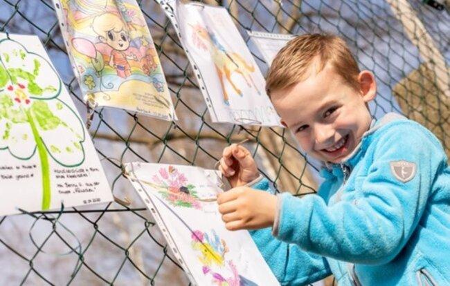 """<p>In der Auerbacher Kita """"Mischka"""" malten die Kinder in der Notbetreuung Bilder für ihre Spielgefährten, von denen sie derzeit getrennt sind. Damit diese sie auch sehen können, wurden die kleinen Kunstwerke am Zaun vor der Einrichtung angebracht - im Foto&nbsp;befestigt Lennox (6) von der Wackelzahngruppe ein Bild.</p>"""