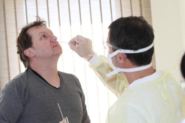 <p>Als erster Patient in der Plauener Corona-Ambulanz wurde am Montag Jens Reinwald (links) getestet. Der Allgemeinmediziner Dr. Udo Junker nahm die Untersuchung inklusive Abstrich vor.&nbsp;</p>