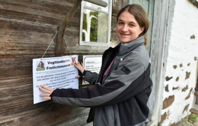 <p>Uta Karrer, Leiterin der Freilichtmuseen in Landwüst und Eubabrunn, bringt Hinweisschilder an. Die Museen dürfen ab Mitte Mai wieder öffnen, aber nur mit Schutzauflagen.</p>