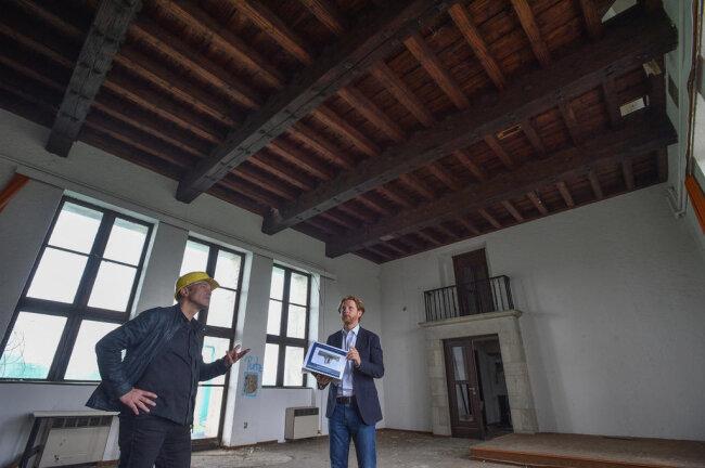 <p>Bauleiter Andreas Hüppe (links) und Baubürgermeister Michael Stötzer im unteren großen Saal. Hier sollen später einmal Empfänge für erfolgreiche Spitzensportler stattfinden. Die Holzdecke soll erhalten werden.&nbsp;</p>