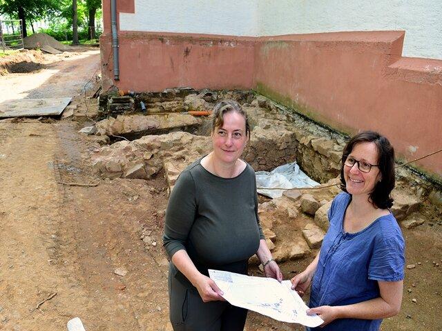 <p>Rebecca Wegener (l.) und Daniela Frehse vor den Resten eines älteren Fundaments an der Außenwand.</p>