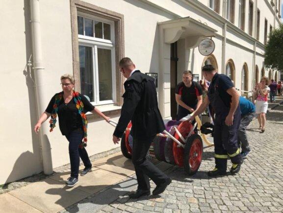 <p>Am Mittwoch hatte die Feuerwehr die Schals auf eine Schlauchtrommel gewickelt und zog mit diesen um den Sitz der Stadtverwaltung.</p>