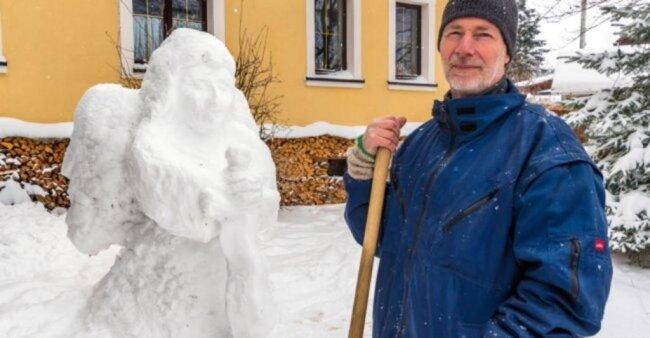 """<p>Einen rund zwei Meter hohen Engel aus Schnee hat Johannes Oettel im Vorgarten seines Hauses im Marienberger Ortsteil Gebirge gebaut. """"Wenn es schneit und abzusehen ist, dass es kalt wird und der Schnee liegen bleibt, lege ich los. Die Idee habe ich im Kopf"""", erläutert der 61-jährige Werkzeugmacher sein Vorgehen. Zuletzt hatte der Erzgebirger kurz vor Weihnachten 2017 Maria und Josef und im Januar 2019 einen Hirten, der mit seinem Kamel an einem Brunnen rastet, als Schneegroßfigur errichtet. Diesmal stellte der gläubige Christ Cherub, den himmlischen Wächter des Paradieses, mit einem Flammenschwert dar. Für den Bau der Engelsfigur benötigte Johannes Oettel nach eigenen Angaben lediglich eine Schaufel, seine Hände und annähernd zwei Stunden Zeit.</p>"""