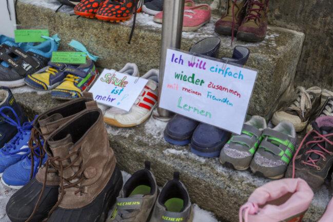 <p>In Thalheim im Erzgebirge haben Eltern Protest eingelegt und zahlreiche Kinderschuhe sowie Plakate vor der Eingangstür zum Rathaus abgestellt.</p>
