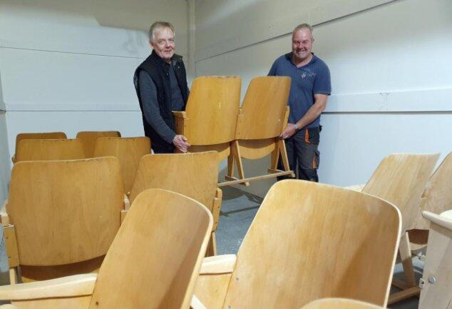 <p>Frank Manteuffel (links) und Thomas John bringen zwei der Holzsitze in Stellung, die aus einem Kölner Kino stammen. Die in den 1950er-Jahren gebaute Einrichtung soll künftig im kleinen Kino des Enduro-Museums den Besuchern Platz bieten. Die Motorradfans und -interessierten werden schon erwartet.</p>