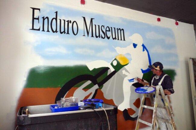 """<p>In Zschopau öffnet bald das neue Motorradmuseum.&nbsp;Beim Eintreten erblickt der Besucher zuerst ein großes Bild. Es&nbsp;wird dem kürzlich verstorbenen Andreas Cyffka gewidmet, der auf MZ große Erfolge feierte. Gemalt wird es von Uwe Häußler, der selbst ein erfolgreicher Geländefahrer war und heute von allen nur """"Picasso"""" genannt wird.&nbsp;</p>"""